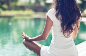 Frau bei ihrer Yogaübung mit Blick auf den Teich