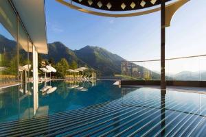 Terrasse mit Pool, Schirmen, Liegestühlen und einer Berglandschaft im Hintergrund