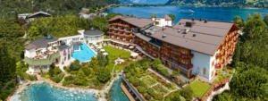 Luftaufnahme vom Hotel Salzburgerhof in Zell am See mit der Hotelanlage im Vordergrund und der Landschaft im Hintergrund