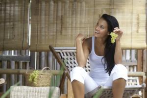 Lächelnde Frau sitz mit einem weißen Outfit und Trauben auf einem Holzstuhl