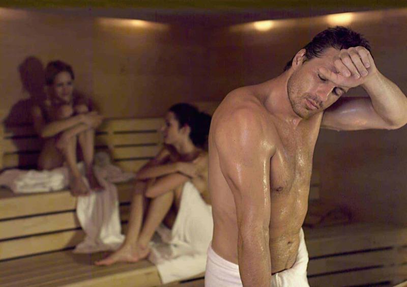 Saunabereich mit drei schwitzenden Personen in der Sauna