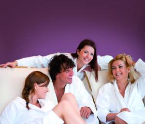 Drei Personen im weißen Bademantel liegend und sitzend auf den Liegestühlen