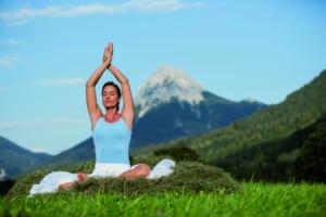 Frau mit einem blauen Top bei ihrer Yogaübung und um Hintergrund befindet sich eine Bergspitze