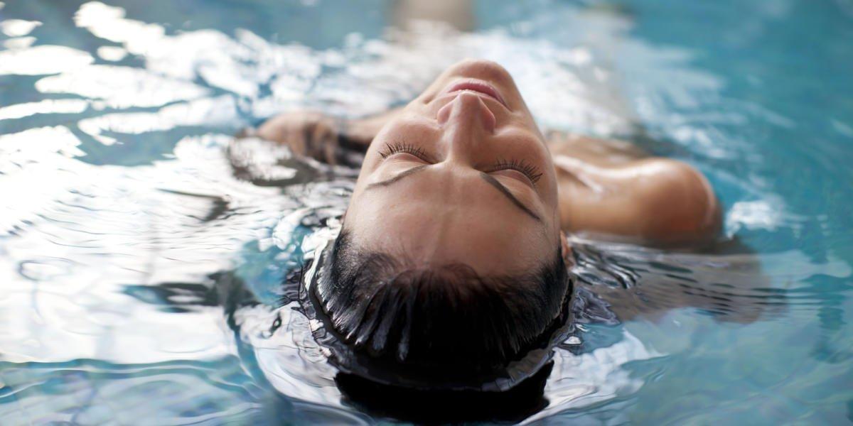 Frau liegend im Pool und genießt ihren Wellnessurlaub