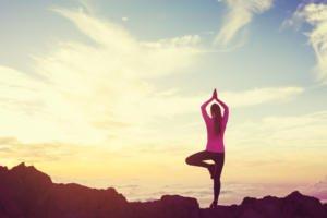 Frau bei ihrer Yogaübung mit Blick auf die Berge
