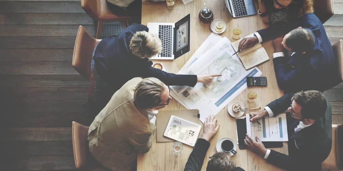 Geschäftsmänner bei der Ausarbeitung eines Projektes auf einem Tisch