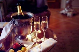 Champagne mit zwei vollen Gläsern auf einem Glastisch