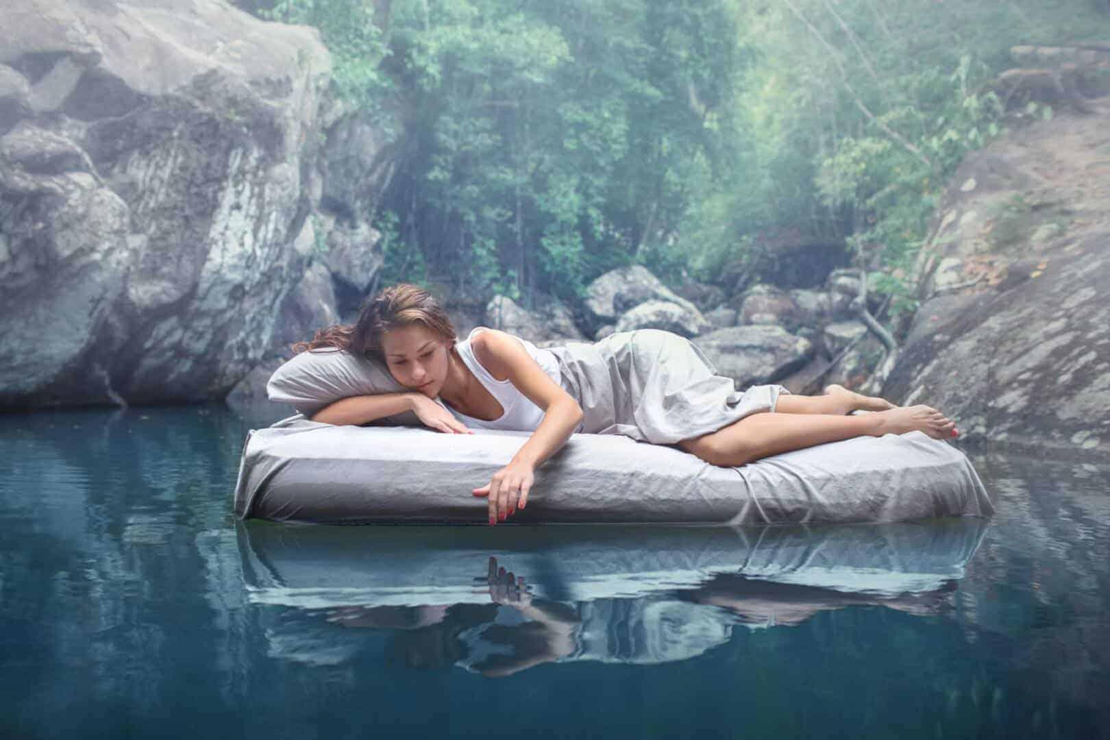 Frau auf einer Luftmatratze in einem kleinen Teich