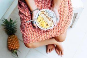 Frau mit gesunder Mahlzeit in einer weißen Schale
