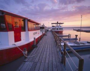 Bootanlegestelle mit einer Radfähre und mehreren kleinen Booten am Steg angebunden