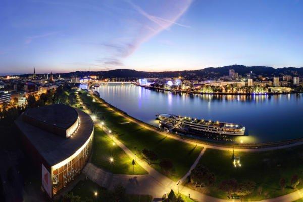 Linz bei Nacht wo die Donau durch die Stadt fließt und das Schiff auf der Anlegestelle ist