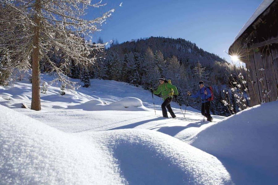 Zwei Tourengeher in einer Schneelandschaft mit den Bergen im Hintergrund