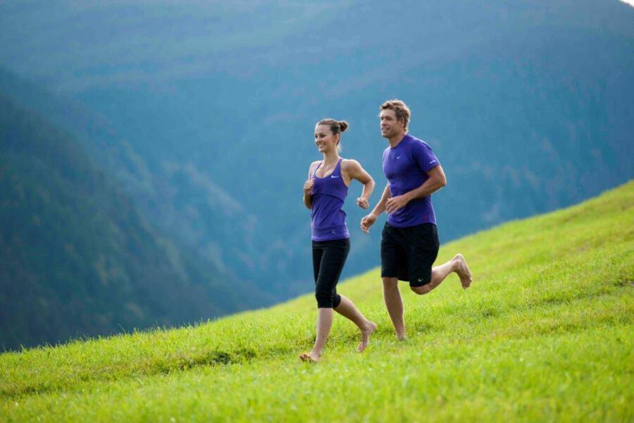 Ein Mann und eine Frau beim Laufen auf dem grünen Feld in den Bergen