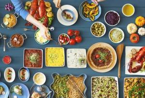Gedeckter Tisch mit verschiedenen Mahlzeiten jeglicher Art und einer Dame die nach dem Essen greift
