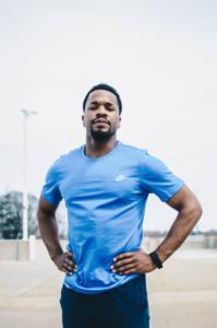 Mann mit einem blauen T-Shirt während der Pause in einer Fitnessübung