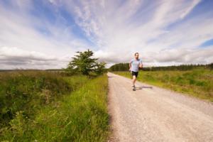 Mann während dem Laufen auf einem Schotterweg und einem Feld mit Bäumen im Hintergrund