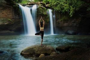 Frau bei der Meditation mit einem Wasserfall im Hintergrund